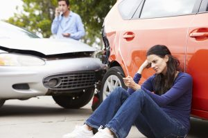 Female Driver Making Phone Call After Traffic Accident Sat Against Car.